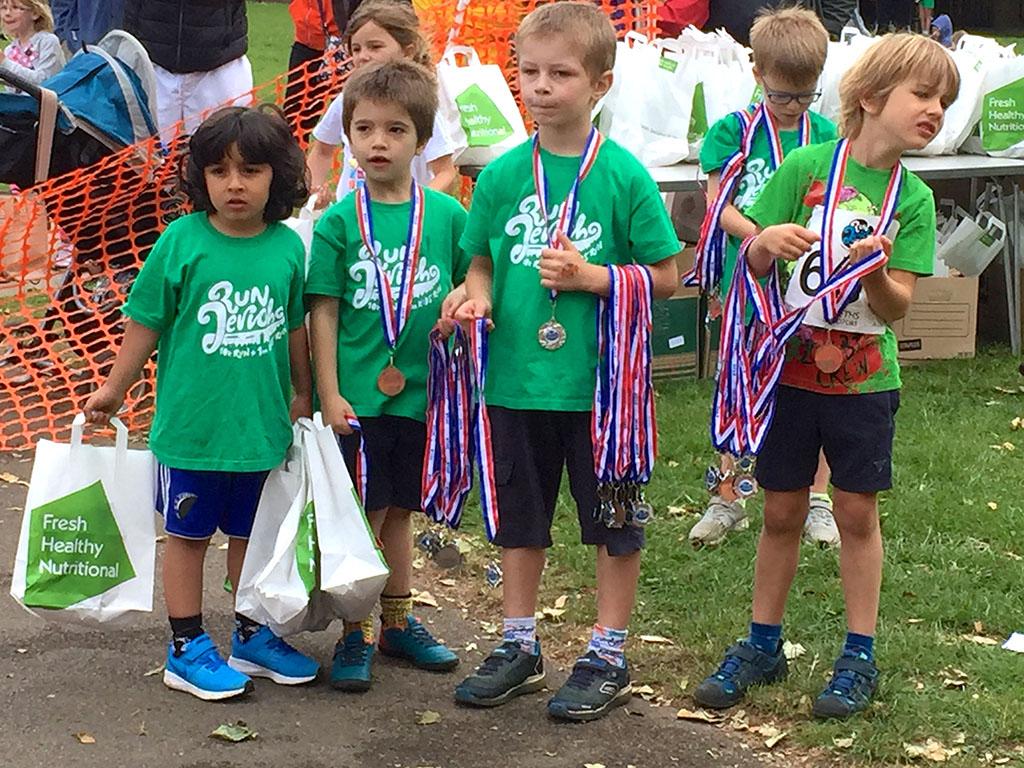 Run Jericho children volunteers handing out medals